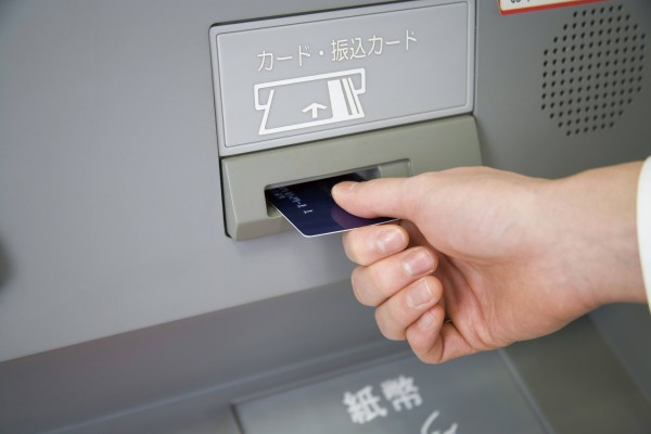 person inserting card into ATM